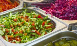 Por que saladas são opções arriscadas em restaurantes desconhecidos?